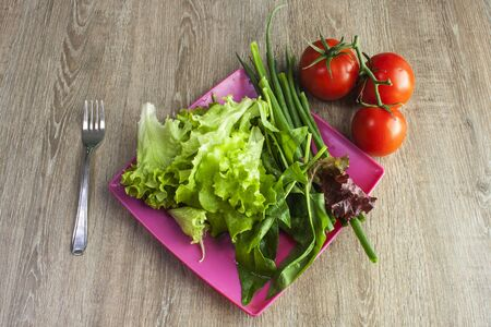 Salad with greens, cherry tomatoes, onions on pink square plate with fork on wooden table, overhead view