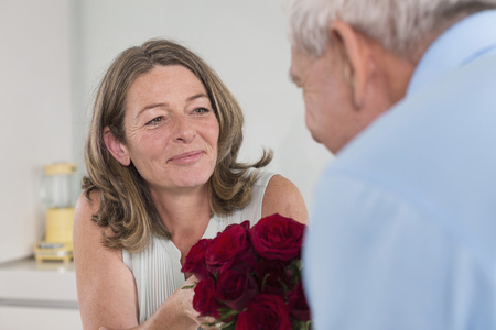 Senior man giving red roses to woman
