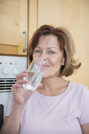 crinkles: Portrait of senior woman in kitchen with water glass, smiling