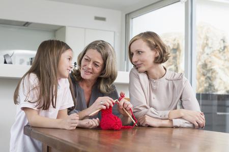Grandmother, mother and daughter knitting together LANG_EVOIMAGES