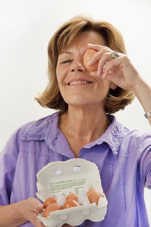 scrutinise: Senior woman holding egg in front of eye, smiling