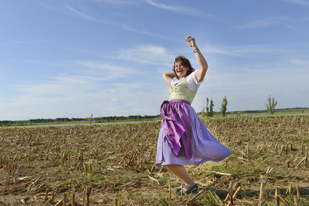 Mature woman dancing in field, Bavaria, Germany LANG_EVOIMAGES