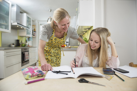 figuring: Mother helping daughter with homework, smiling