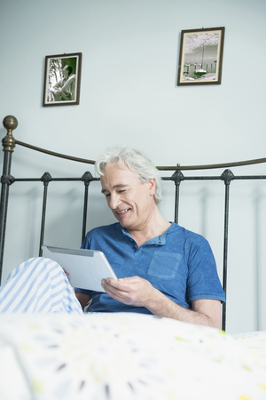 time sensitive: Mature man sitting in bed and using digital tablet, smiling