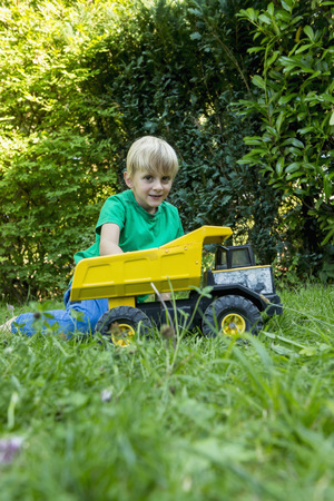 cowering: Young boy playing with toy car in the garden LANG_EVOIMAGES