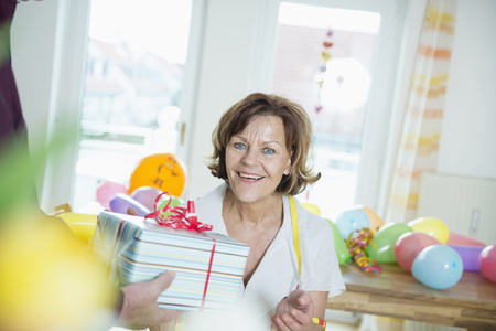 crinkles: Senior man hand over present to woman on birthday, smiling