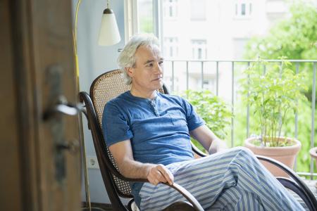 pyjama: Mature man sitting in rocking chair, looking away