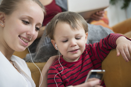 mp3 player: Sister listening to mp3 player with her brother, smiling LANG_EVOIMAGES