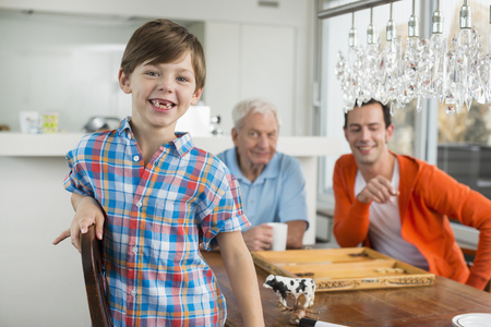 Happy boy with father and grandfather in background LANG_EVOIMAGES