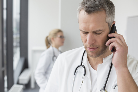 Doctor on phone while female doctor in background
