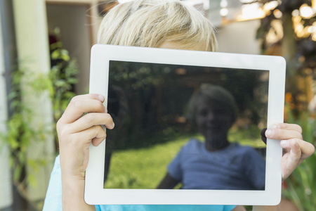 10 11 years: Young boy hiding his face behind tablet computer