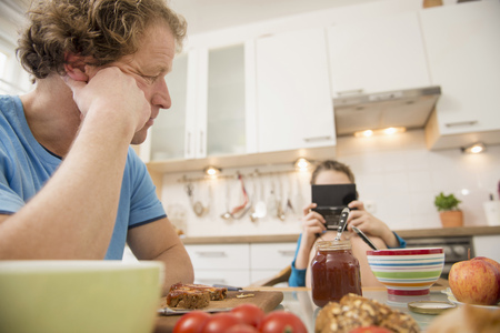 niños desayunando: Father looking at son playing video game at breakfast table LANG_EVOIMAGES
