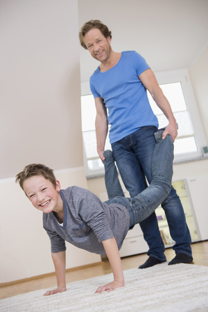ardor: Father and son having a wheelbarrow race at home