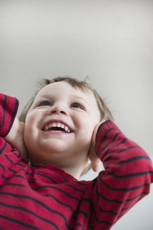 twee: Boy covering ears, smiling