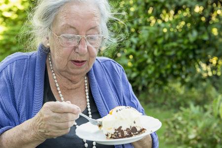 crinkles: Female senior eating cream cake