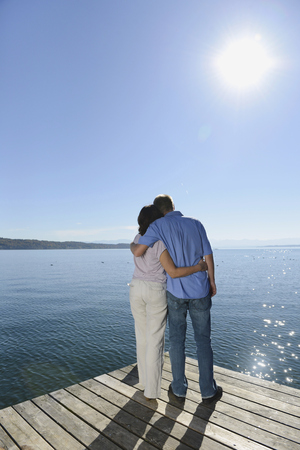Mature couple standing and embracing each other on boardwalk, Bavaria, Germany LANG_EVOIMAGES