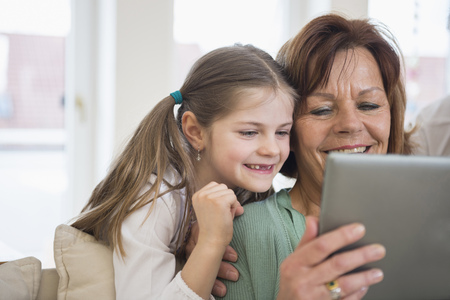 Grandmother and granddaughter looking in digital tablet, smiling LANG_EVOIMAGES