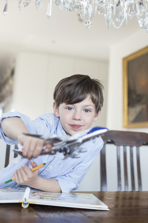 chandelier  kids: Portrait of boy playing with model airplane, smiling
