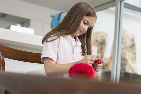 Smiling brunette girl knitting LANG_EVOIMAGES
