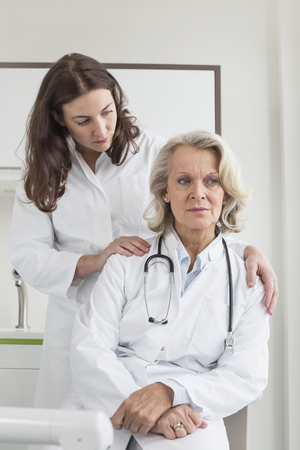 overstress: Female doctor consoling collegue