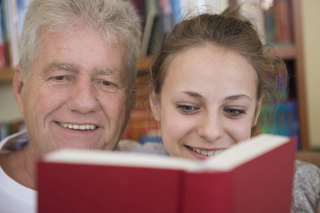crinkles: Grandfather and granddaughter reading book on couch in living room, smiling LANG_EVOIMAGES