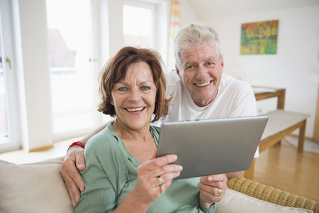 time sensitive: Portrait of senior couple with digital tablet, smiling LANG_EVOIMAGES