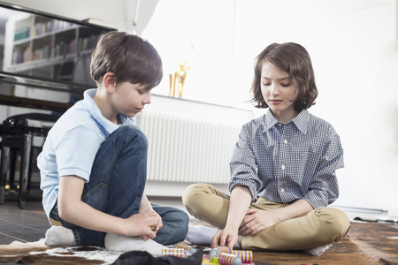 sitting on the ground: Girl and boy playing board game