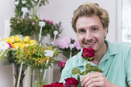 Portrait of mid adult man holding red rose, smiling LANG_EVOIMAGES