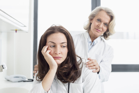 collegue: Female doctor consoling collegue