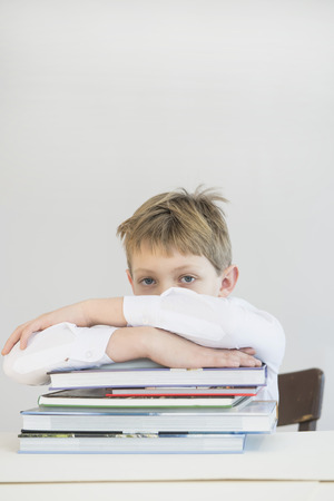 overstress: Frustrated boy with stack of books, close up