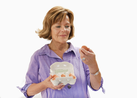 scrutinise: Senior woman holding eggs, close up