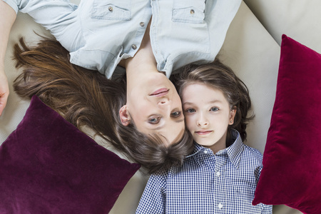 first day: Portrait of mother and daughter lying on floor, smiling