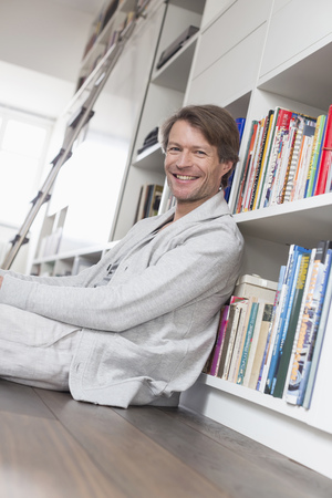 sitting on the ground: Portrait of mature man sitting in front of bookshelf, smiling
