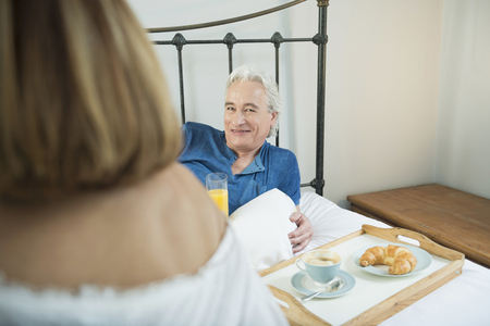 60 65 years: Couple having breakfast in bed, smiling