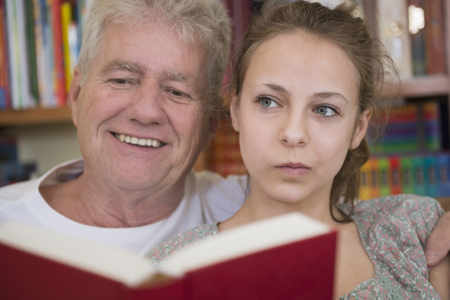 Grandfather and granddaughter reading book on couch in living room, smiling LANG_EVOIMAGES