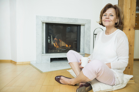 tailor seat: Portrait of senior woman sitting in front of fireplace, smiling