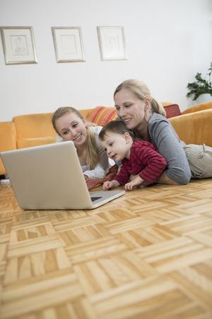 upper floor: Family using laptop in living room, smiling