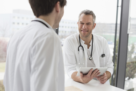 Doctors having conversation with digital tablet