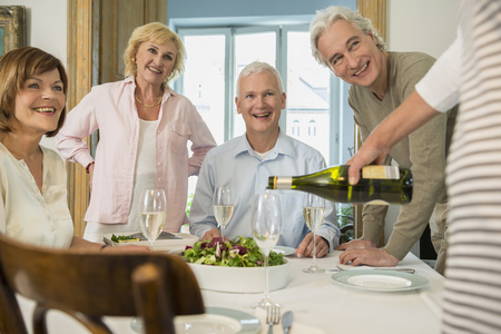 white wine: Woman pouring sparkling wine into glasses for her friends, smiling LANG_EVOIMAGES