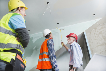 building regulations: Architect and two construction workers at construction site of new building