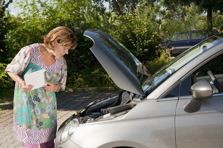 60 65 years: Senior woman standing near brake down car with her digital tablet LANG_EVOIMAGES