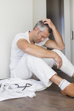 overstress: Unhappy doctor sitting on floor
