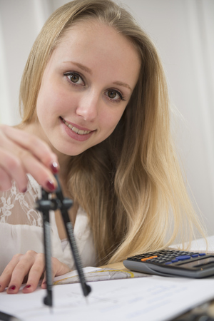 figuring: Teenage girl doing homework, smiling LANG_EVOIMAGES