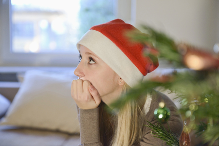 Thoughtful teenage girl in front of christmas tree LANG_EVOIMAGES