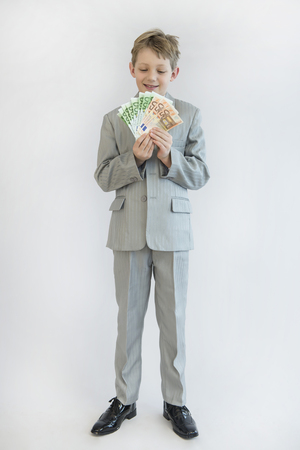 Boy holding paper money in his hand, smiling, portrait LANG_EVOIMAGES