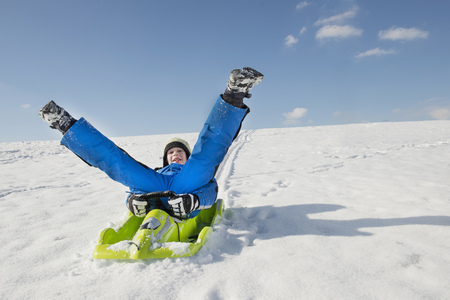 anorak: Boy sledging down hill, smiling, Bavaria, Germany