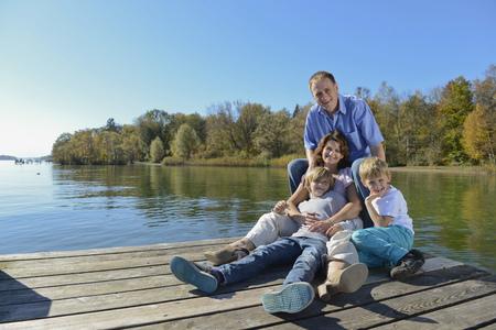 Family sitting on boardwalk, smiling, Bavaria, Germany