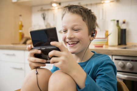 beings: Boy playing video game in kitchen