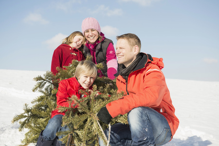 cowering: Family sitting with branches in winter, smiling, Bavaria, Germany