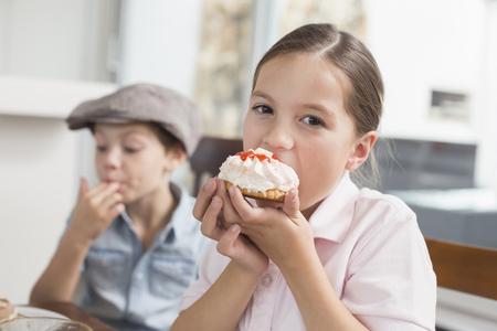 Brunette girl eating cake, portrait LANG_EVOIMAGES